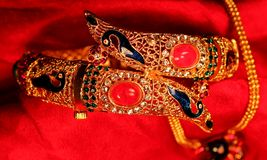 Golden Indian bracelet in red background Stock Images