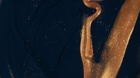 Golden ink particles flows in water as colorful chaos on the black background