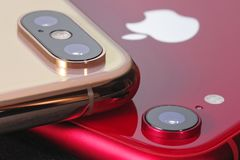 Golden iPhone XS Max and red iPhone XR royalty free stock photos