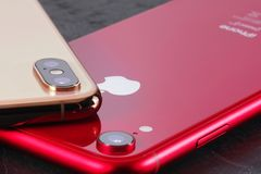 Golden iPhone XS Max and red iPhone XR stock photo
