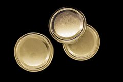 Golden jar lids isolated on black background stock photo