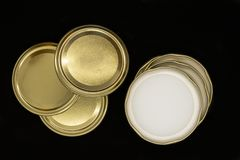 Golden jar lids isolated on black background stock photos