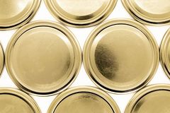 Golden jar lids on white background stock photography
