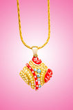 Golden jewellery against pink gradient background Royalty Free Stock Images