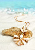 Golden jewellery pendant  on sand beach with sea background, sof Stock Photos