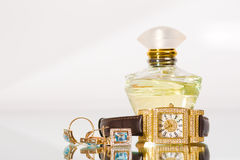Golden jewellery and perfume Stock Photos