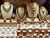 Golden jewellery in a shop. Closeup of golden jewellery in a shop or store window royalty free stock photo