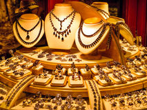 Golden jewellery in a store window. Expensive golden jewellery for sale in a shop or store window stock photography