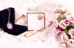 Golden jewelry in box and flowers Stock Images