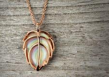 Golden jewelry pendant on grey wood background Royalty Free Stock Photo