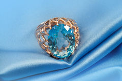 Golden jewelry ring with blue topaz Stock Image