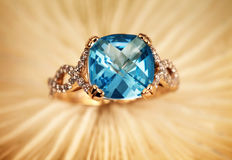 Golden jewelry ring with blue topaz Stock Images