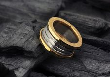 Golden Jewelry ring with diamonds, on black coal as background stock images