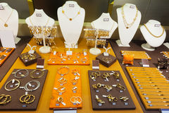 Golden jewelry in store window. Counter with golden jewelry in store window stock image