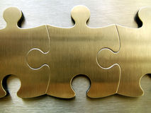 Golden jigsaw network. Golden jigsaw piece on a metallic background royalty free stock photo