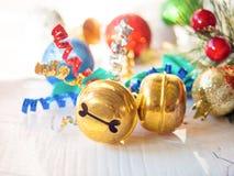 Golden jingle bells for christmas decoration. Golden jingle bells on white wooden table  for christmas decoration Stock Images