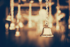 Golden jingle bells hanging in the dark background with vintage filter Stock Photos