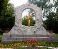 Golden Johann Strauss statue Vienna. Golden Johann Strauss statue in the city park with flowers in Vienna Stock Images