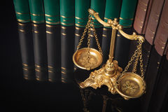 Golden justice scales in front of law books Royalty Free Stock Images