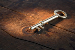 Golden Key. Closeup of vintage golden key lying on old wooden surface with beam of light Stock Image