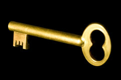 Golden key. A shiny old-style golden key isolated on black background Stock Photography