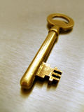 Golden key. On a metallic background (conceptual royalty free stock photography