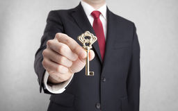 Golden key in businessman hand Stock Photography
