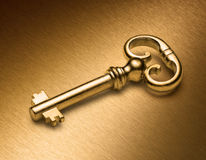 Golden Key On Gold. A gold skeleton key on a bronze coloured metal background Royalty Free Stock Photos