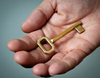 Golden key in a hand. Stock Photo