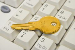 Golden key on keyboard Stock Images