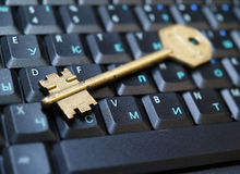 Golden key on laptop1 Stock Photos