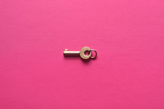 Golden key on a pink background. Golden key on a pink background, top view. Trendy colorful photo. Minimal style with colorful paper backdrop. Flat lay fashion Stock Photography