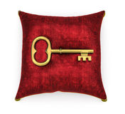 Golden key on royal red velvet pillow isolated on white backgrou Royalty Free Stock Photo