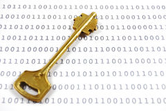 Golden key on a sheet with binary encrypted data stock images