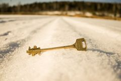 The Golden key to the door lies in the snow royalty free stock image