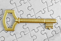 Golden Key to the puzzle. Stock Photo