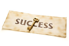 Golden key to success. A golden key placed over an vintage paper with word 'success' printed on it Royalty Free Stock Photography