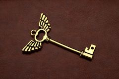 Golden Key with wings on Brown Leather Royalty Free Stock Photo