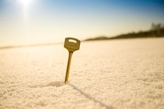 Golden key. Winter day! Beautiful Golden key shimmers in the sun.That key in the snow. it is sticking out of the white drifts.He needs to open the door.The Royalty Free Stock Image