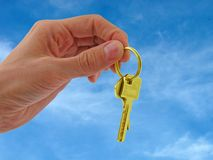 Golden keys. Hand with golden keys over blue sky Stock Photography