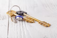 Golden keys to the apartment on wooden background royalty free stock photos