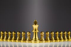 The golden king of chess stands out from the hordes of pawns behind it. Concept of leadership and success in business competition