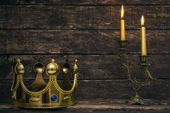 Golden king crown and burning candle on the table. Burning candle and king golden crown on aged wooden table background royalty free stock image