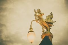 Golden Kinnaree on light pole sky cloud. royalty free stock photos