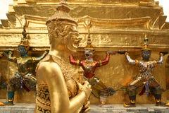 Golden kinnari bangkok grand palace thailand. Golden kinaree statue in front of golden architecture in bangkoks grand palace in thailand Stock Images