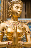 Golden Kinnari statue at Temple of Emerald Buddha. Bangkok, Thailand royalty free stock images