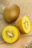 Golden kiwifruit/ kiwi cut and whole. Whole and cut golden kiwifruit/ kiwi (Actinidia chinensis) on white background Stock Photos