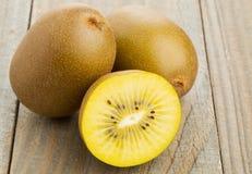 Golden kiwifruit/ kiwi cut and whole. Whole and cut golden kiwifruit/ kiwi (Actinidia chinensis) on wooden cutting board Royalty Free Stock Images