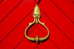 Golden knocker on the red door Royalty Free Stock Photos