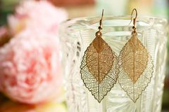 Golden ladies earrings leaves close up on blurred colorful background with flowers stock photography